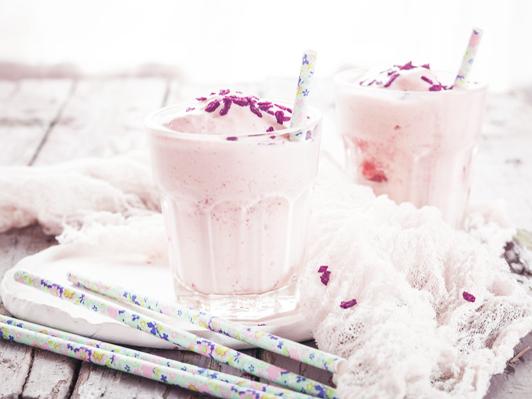 Two glasses of vanilla milkshake with dried raspberries